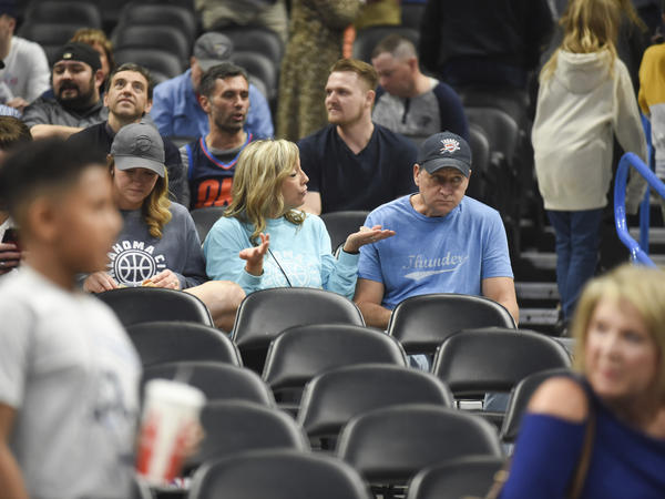 Basketball fans react after it is announced that an NBA basketball game between Oklahoma City Thunder and Utah Jazz in Oklahoma City has been postponed on Wednesday, March 11.