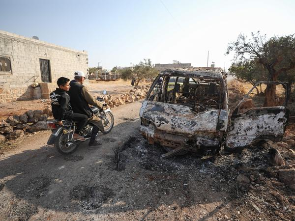 Syrians ride a motorcycle past a burned vehicle near the village of Barisha in the Idlib province of Syria, near where U.S. forces raided the compound of ISIS leader Abu Bakr al-Baghdadi. Local residents tell NPR that noncombatant civilians were killed and injured in the van the night of the U.S. raid.