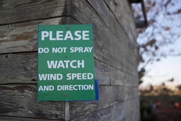 File photo. A sign at the property of Eric and Mari Perez in Qunicy, Washington, where houses are surrounded by apple orchards. Some people don't want the pesticide chlorpyrifos drifting from orchards to their property.
