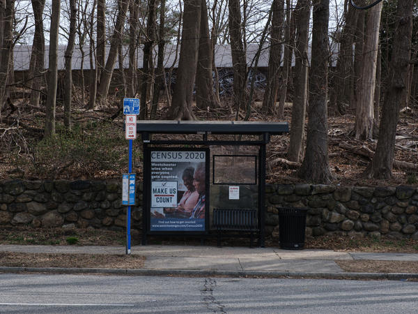 A bus stop with a poster promoting the 2020 census sits empty in New Rochelle, N.Y., a New York City suburb where National Guard members were sent to try to slow the spread of the coronavirus outbreak.