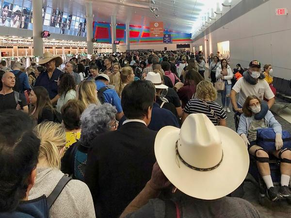 People wait in line to go through customs at Dallas/Fort Worth International Airport on Saturday. International travelers reported long customs lines at the airport Saturday as staff took extra precautions to guard against the new coronavirus.
