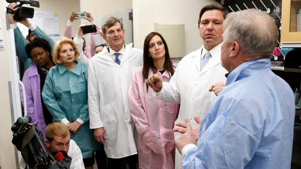 Florida Gov. Ron DeSantis, second from right, and Lt. Gov. Jeanette Nunez, third from right, discuss the coronavirus testing in Florida during a visit to a Tampa lab on March 2, 2020.