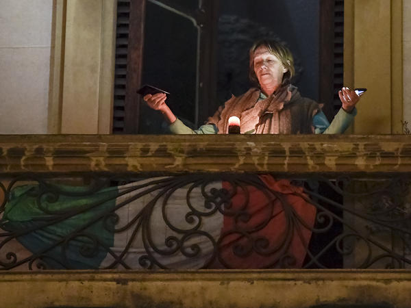 A woman holds lights on her balcony during a flash mob launched throughout Italy on Sunday to bring people together even as they are staying home in an effort to halt the spread of the coronavirus.