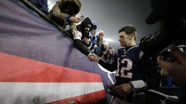 Tom Brady shakes hands with a fan as he leaves the field in Foxborough, Mass., after losing a playoff football game to the Tennessee Titans earlier this year. As it turns out, that was likely the final game the quarterback would play in a New England Patriots uniform. He announced his departure Tuesday.