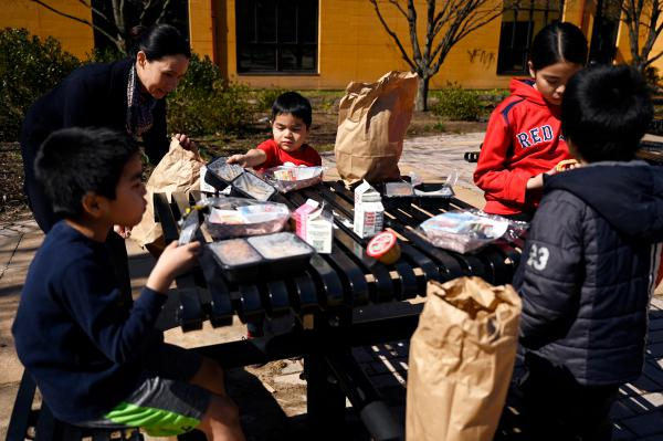 Dr. Leslie Torres-Rodriguez, superintendent of Hartford public schools, helps a young child with his meal served by the district's food and child nutrition services at Samuel Valentin Arroyo Recreation Center.
