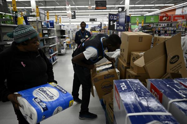 Stella Darko of East Hartford, left, gets a package of bathroom tissue from the last box at a Walmart in Avon. Maintenance Supervisor Micali Marison, right, restocked over 6 pallets and the shelves are close to empty again.