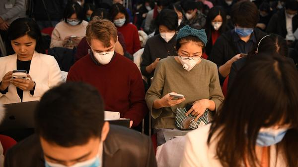 Journalists wearing face masks — in an effort to protect against the coronavirus — gather for a news conference earlier this year in Beijing. Early Wednesday, China said it was planning to pull the press credentials of certain journalists employed by a handful of major U.S.-based newspapers.