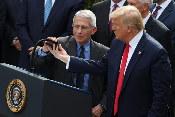 U.S. President Donald Trump adjusts the microphone for National Institute Of Allergy And Infectious Diseases Director Anthony Fauci during a news conference where Trump announced a national emergency in response to the ongoing global coronavirus pandemic in the Rose Garden at the White House March 13, 2020 in Washington, DC.  (Chip Somodevilla/Getty Images)