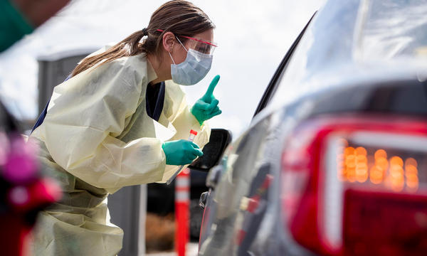 Drive-through screening stations are opening up in several parts of the country as testing capacity starts to expand nationally. At one station in Meridian, Idaho, nurse Ashley Layton communicates with a patient before taking a swab sample.