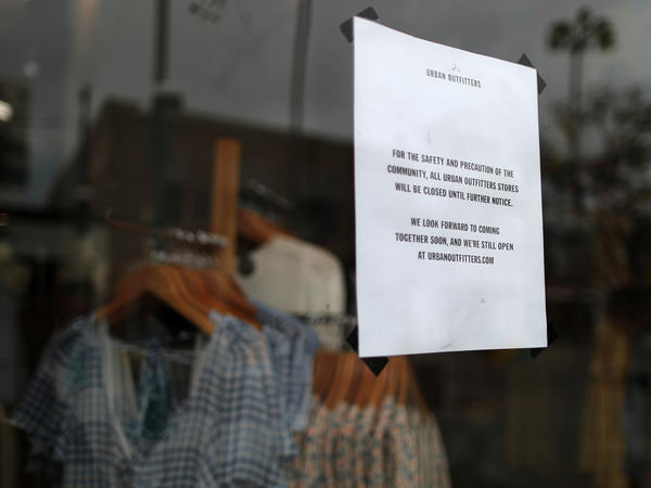 An Urban Outfitters store displays a closed sign in Santa Monica, Calif. With businesses shutting down around the country, a flood of new unemployment claims are pouring in.