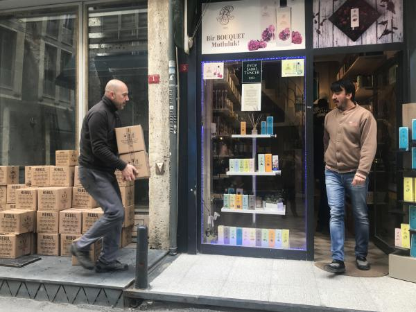 Shop owner Goksel Kaygin (left) and a colleague take in a new delivery of colognes to his shop in Istanbul, Turkey.