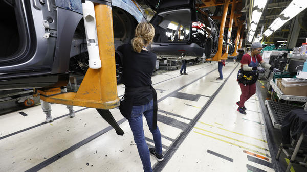 Vehicles go through the assembly line at a General Motors assembly plant in Lansing, Mich., on Feb. 21. GM is assessing the feasibility of converting its plants to make medical equipment.