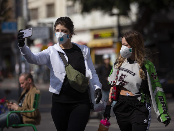 Women take a selfie as they wear face masks in Tel Aviv, Israel, on Sunday. ‏Israel has imposed a number of tough restrictions to slow the spread of the new coronavirus. Now the government is carrying out cellphone surveillance of people who may have come into contact with the virus.