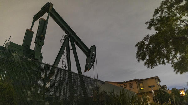 Pump jacks draw crude oil from the Long Beach Oil Field near homes in Signal Hill, Calif., on March 9. The world's crude oil supply is rising even as demand is cratering.