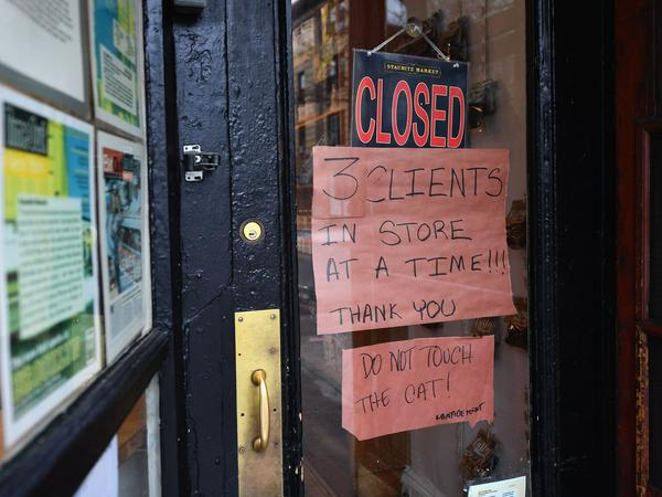 """A butcher shop in the Brooklyn borough of New York shows a """"Closed"""" sign, limiting customers to three at a time. Gov. Andrew Cuomo is ordering all nonessential businesses to close, in an escalation of the state's attempts to contain the COVID-19 pandemic."""
