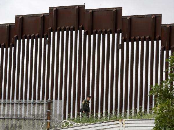 A Border Patrol agent walks along a border wall separating Tijuana, Mexico, from San Diego earlier this week. Travel between the U.S. and Mexico will halt as of Saturday to try to stop the spread of the coronavirus.