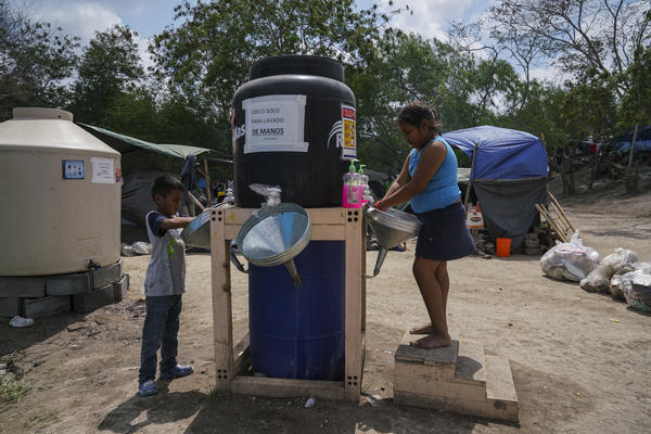 Asylum-seeking children wash their hands at the migrant camp where they live in Matamoros, Mexico on March 17, 2020.