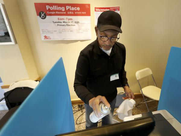 John Davis, a polling judge volunteer, sanitizes an electronic voting machine screen amid concerns about the COVID-19 coronavirus at a polling place in the Bronzeville neighborhood of Chicago, Tuesday, March 17.