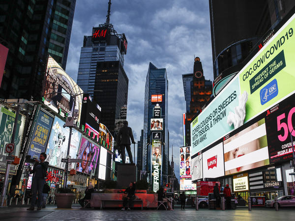 A large screen displays guidance about COVID-19 at a sparsely populated Times Square in New York City on Friday. New York Gov. Andrew Cuomo has ordered all nonessential businesses to close by Sunday.