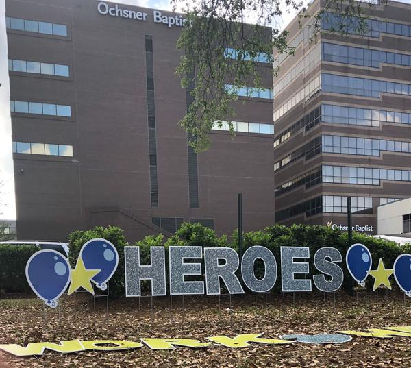 Outside Oshner Baptist hospital in New Orleans, a volunteer puts up decorations celebrating healthcare workers helping combat the coronavirus.
