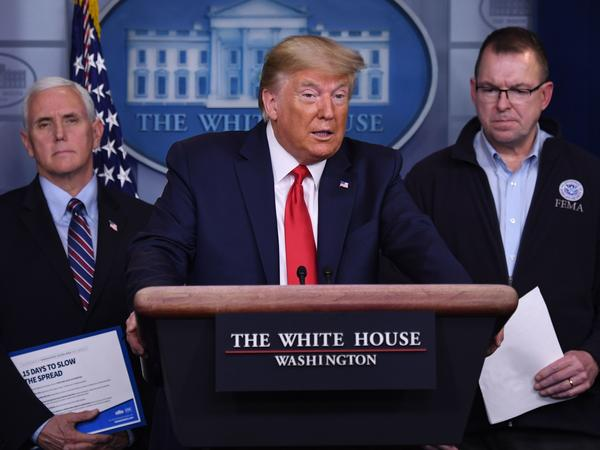 President Trump, flanked by FEMA Administrator Peter Gaynor (right) and Vice President Pence, speaks during a daily briefing on the coronavirus.