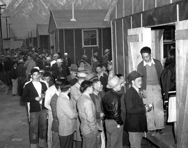 People of Japanese descent wait in line for their assigned homes at an internment camp reception center in Manzanar, Calif., the same camp in which John Tateishi was detained as a child.