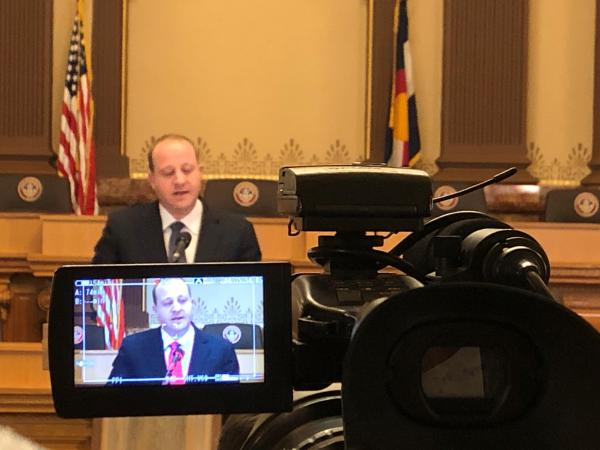 Gov. Jared Polis talks to reporters at the state Capitol in 2019.