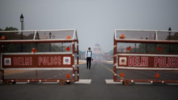 A man walks a deserted road in New Delhi. Indian Prime Minister Narendra Modi asked Tuesday that residents across the country stay where they are in order to help stem the spread of the coronavirus and the deadly disease it can cause, COVID-19.