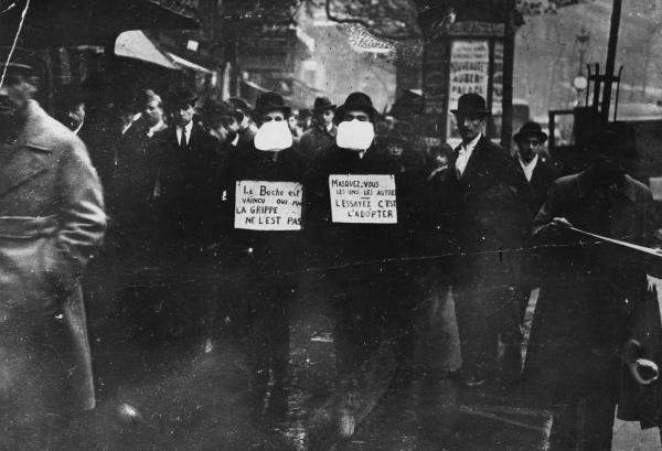 Two men wearing and advocating the use of flu masks in Paris during the Spanish flu epidemic which followed World War I.  (Topical Press Agency/Getty Images)