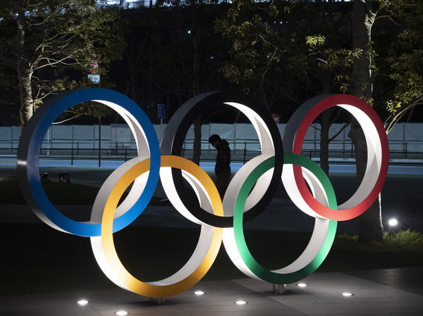 A man is seen through the Olympic rings in front of the New National Stadium in Tokyo, on Tuesday. The Summer Games have been delayed amid the coronavirus pandemic.