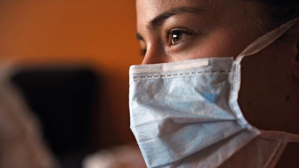 A woman wearing a protective mask watches television in her home.