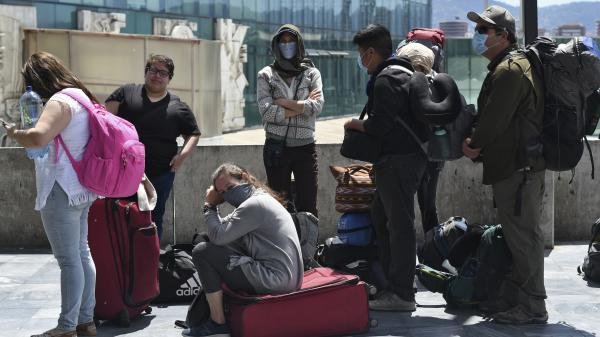 Travelers wait for a charter flight coordinated by the United States embassy to take them home from Guatemala City on Monday.