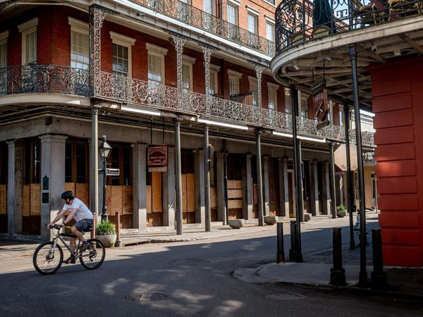 A man cycles along Jackson Square in New Orleans on Thursday. The city has become an epicenter of the coronavirus pandemic gripping the United States.