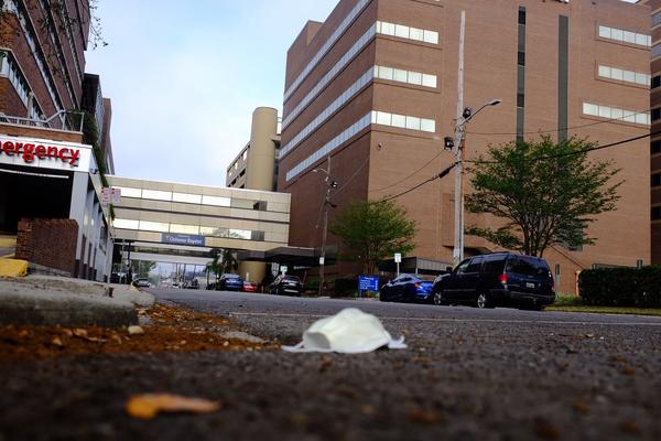 A discarded face mask lies on the ground outside Ochsner Baptist Medical Center in New Orleans. March 25, 2020.