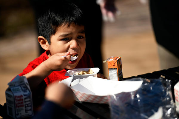 A child digs into his meal served by the Hartford, Conn., school system at a city recreation center on March 16, 2020. School is closed, but the district is continuing to provide meals.