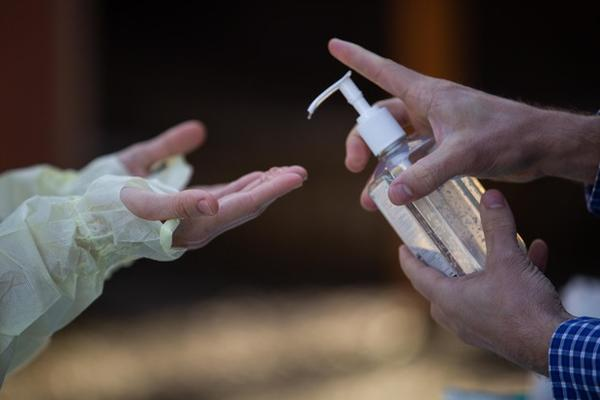 <p>Oregon Health & Science University nurse practitioner Shelby Freed (left) sanitizes her hands between glove changes on Friday, March 20, 2020, in Portland, Ore. Testing for COVID-19 requires regular changing out of PPE like gloves, masks and gowns, but a nationwide shortage has prevented many health care workers from doing so.</p>