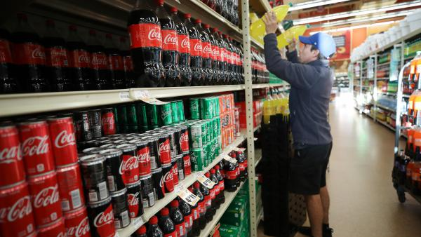 A worker restocks sodas at a Hispanic specialty supermarket in Los Angeles on March 19. Nationally, sales of soft drinks were up 43% that week, compared with the same week in 2019.