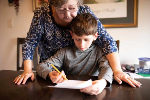 Noah, a fifth grader in West Valley School District, works with his grandmother Sherry Kirksey on math at the kitchen table as school doors remain closed during the coronavirus pandemic.