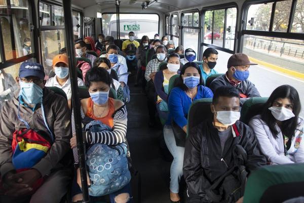 CORONA-CONSEQUENCES Venezuelans on a bus in Caracas wear facemasks to ward off COVID-19.
