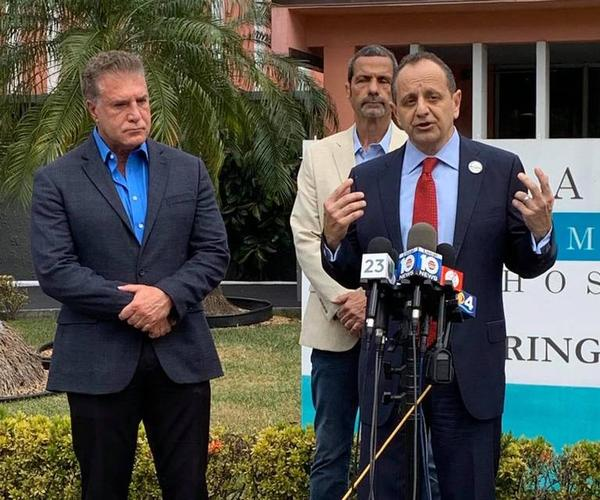 In this photo posted on the Facebook page of Jack Michel, CEO of Larkin Community Hospital, Michel and Hialeah Mayor Carlos Hernandez, left, announce the opening of a drive-thru testing site at Hialeah Hospital.