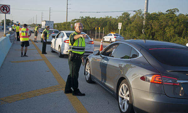 Monroe Sheriff's Office Col. Lou Caputo talks to a driver at the Florida Keys checkpoint on Friday.