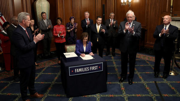 House Speaker Nancy Pelosi, surrounded by a bipartisan group of members of the House, signs the CARES Act on March 27.