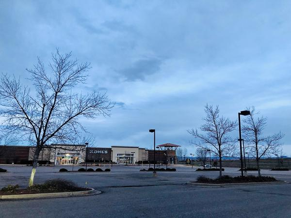 A shopping center parking lot in Littleton was mostly empty on Sunday, March 29 except for a State Patrol vehicle. The state remains on a stay-at-home order through April 11.