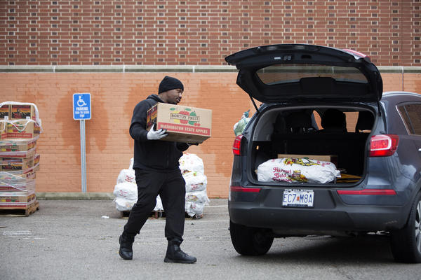 A staff member loads up food donations for a church group at an emergency food distribution center set up outside Better Family Life.