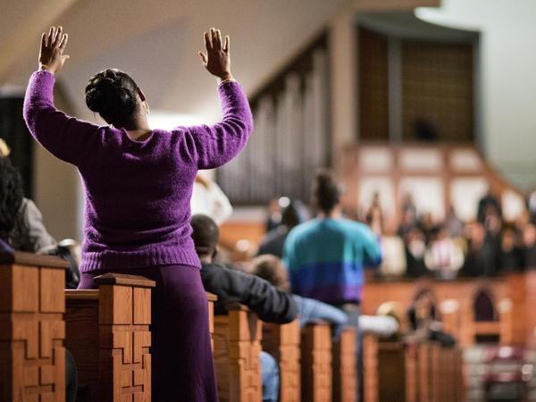 A woman raises her hands during an interfaith service at Ebenezer Baptist Church, the church where The Rev. Martin Luther King Jr. used to preach.
