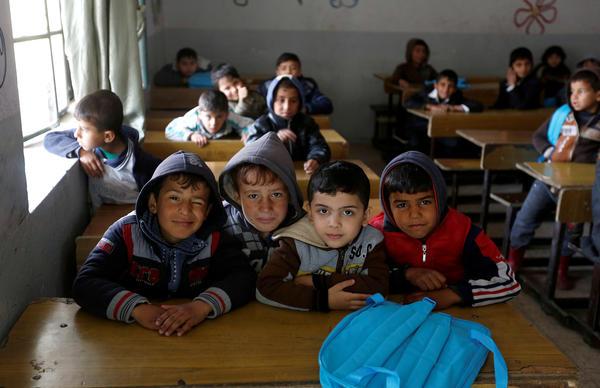 Schoolchildren pose for a photo in a classroom at the al-Kufa school in Mosul.