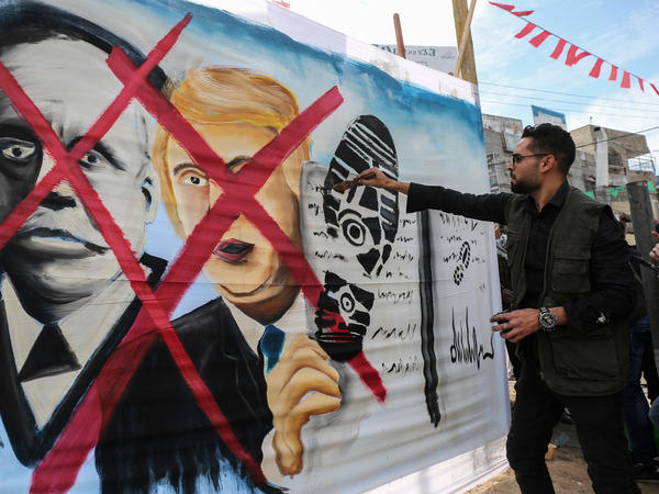 A Palestinian paints a picture showing President Trump and the sole of a shoe in the Gaza Strip on Wednesday.