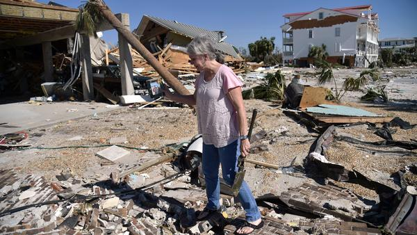 In the aftermath of Hurricane Michael last year, a woman tries to recover belongings from the place where her house once stood in Mexico Beach, Florida.