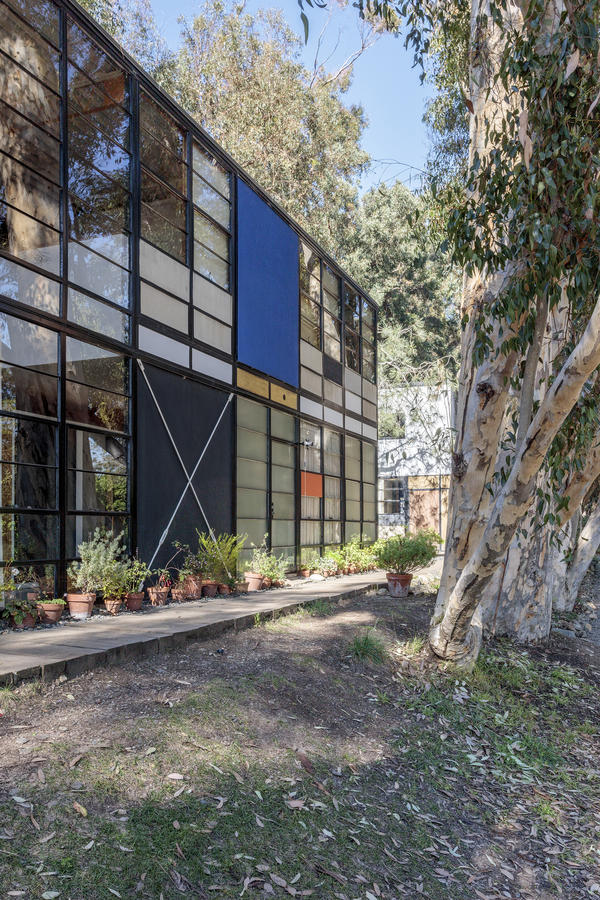 The exterior of the house is composed of glass windows and painted walls, framed by black steel beams.