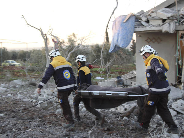 In this photo provided by the Syrian Civil Defense White Helmets, Syrian White Helmet civil defense workers carry a victim next to a destroyed house that was hit by Russian airstrikes, in Maaret Musreen village, in Idlib province, Syria, on Thursday.